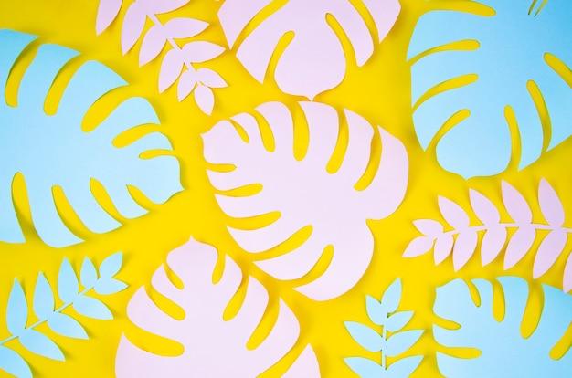 Piante tropicali nello stile della carta tagliata su fondo giallo