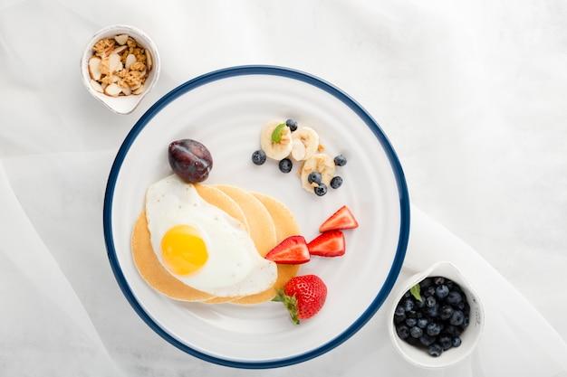 Piastra colazione vista dall'alto con uova e frittelle