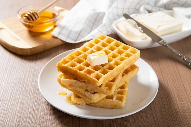 Piastra con deliziosi waffle con miele e una fetta di burro. avvicinamento