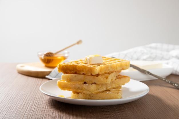 Piastra con deliziosi waffle con miele e una fetta di burro