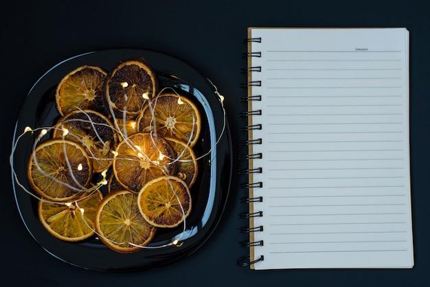 Piastra con fette di arancia essiccata e ghirlanda che brucia con il taccuino in bianco
