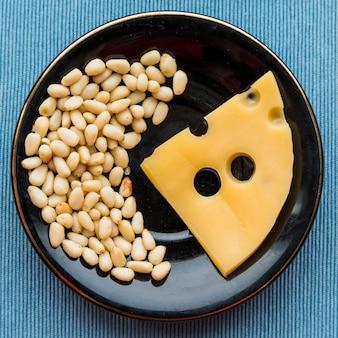 Piastra con formaggio fresco e mucchio di noci sul tavolo