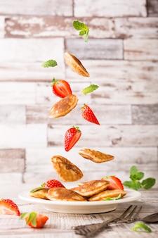 Piastra con mini frittelle olandesi chiamati poffertjes e ingredienti volanti