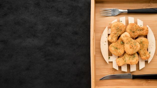 Piastra con pepite di pollo sul vassoio in legno