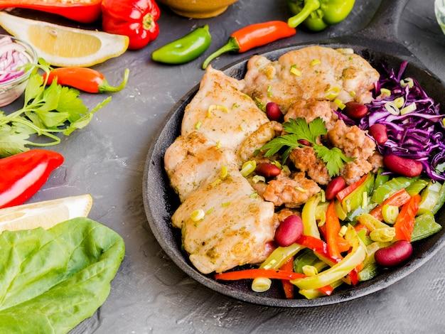 Piastra con piatto di carne vicino a verdure e limoni