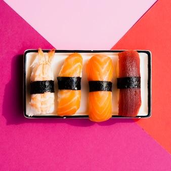 Piastra con sushi su uno sfondo rosa e rosso