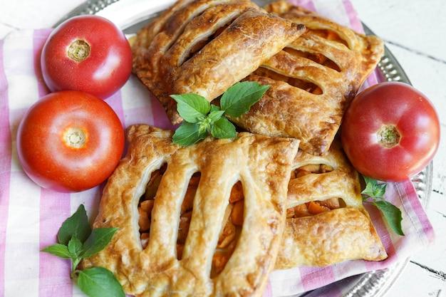 Piastra con torte fatte in casa e pasta sfoglia con pomodori sul tavolo