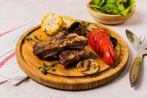 Piastra con verdure grigliate e carne sul tavolo
