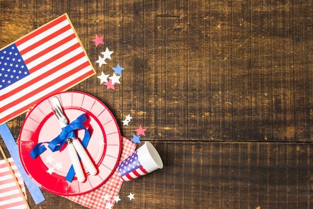 Piastra di bandiera usa e posate legate con nastro blu con bandiera; stella e tazza monouso sulla scrivania in legno