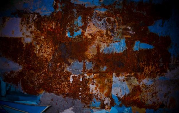 Piastra di metallo arrugginito con rosso saturo e blu al muro del negozio di alimentari