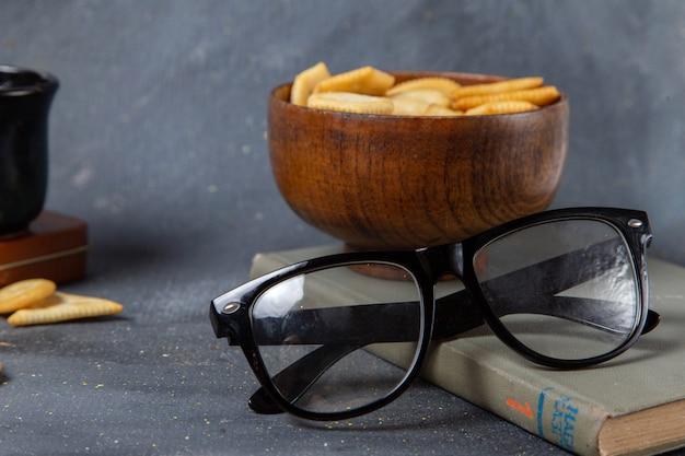 Piastra di vista frontale con cracker con occhiali da sole su grigio