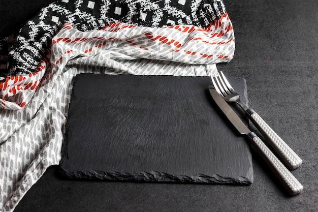 Piastra in ardesia nera con forchetta e coltello su superficie nera e tovaglia.