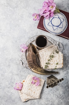 Piastra metallica con matzah o matza, kiddush cup, corno shofar su uno sfondo chiaro presentato come festa seder pasquale o pasto con spazio di copia. oggetti tradizionali ebraici, yarmulke, tallit, libro di preghiere