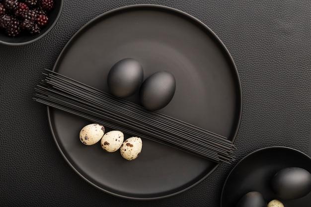 Piastra vista dall'alto con pasta al nero di seppia e tipi di uova