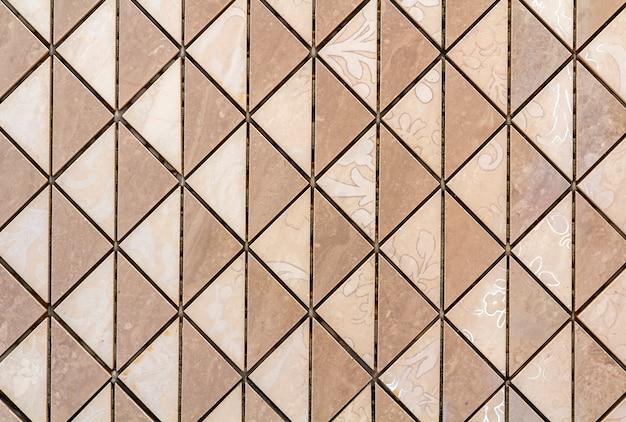 Piastrelle beige a parete o pavimento con decorazioni floreali chiare. ripetendo la progettazione grafica, superficie piana, sfondo geometrico.