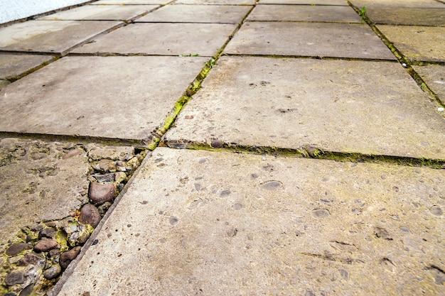 Piastrelle per pavimento di calcestruzzo incrinate vecchie e rotte