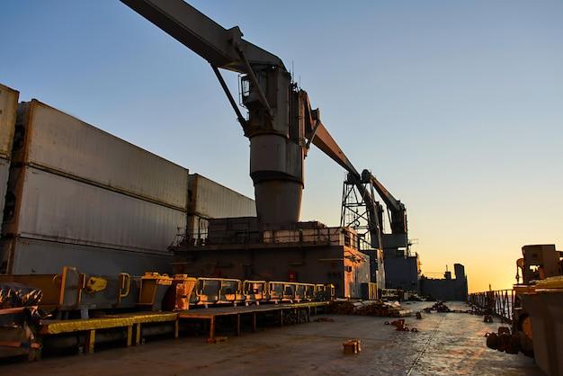 Piattaforma della nave da carico con gru e container al tramonto