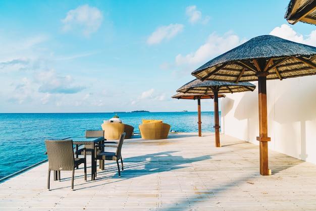 Piattaforma e sedia vuote all'aperto del patio con l'oceano blu in maldive