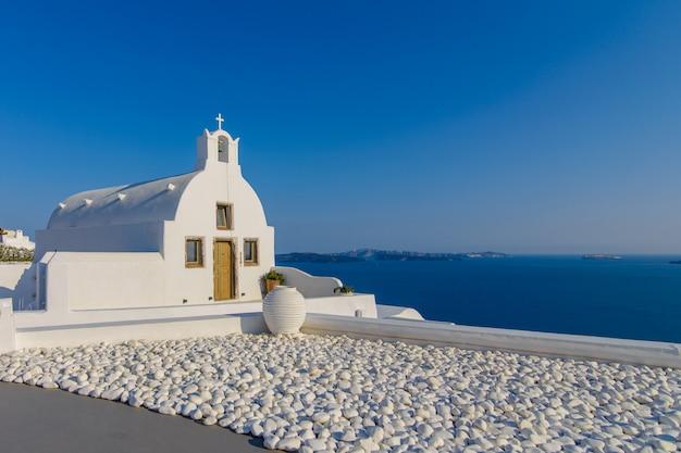 Piattaforma panoramica e camera d'albergo con vista sul mare e sulla città di oia, santorini.
