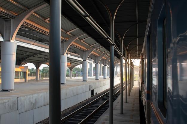 Piattaforma passeggeri con fermata del treno sulla stazione ferroviaria al tramonto