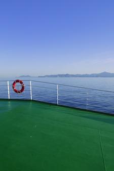 Piattaforma verde della barca con le montagne dell'isola di ibiza