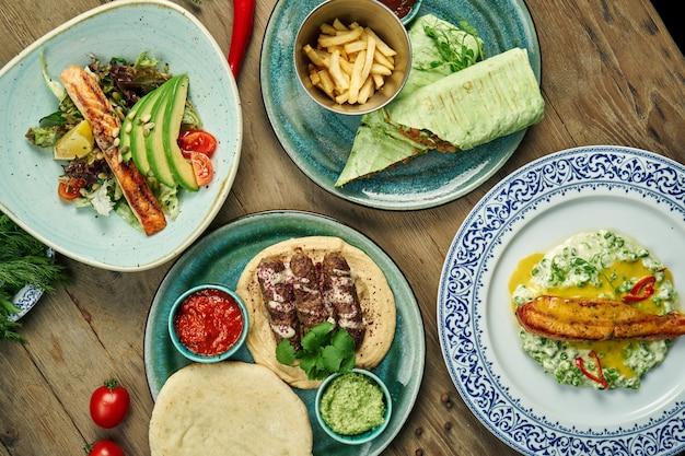 Piatti assortiti della cucina orientale e mediterranea - bistecche di salmone alla griglia con insalate, shawarma, keulab di lyulya con hummus. tavolo da pranzo con vista dall'alto di cibo