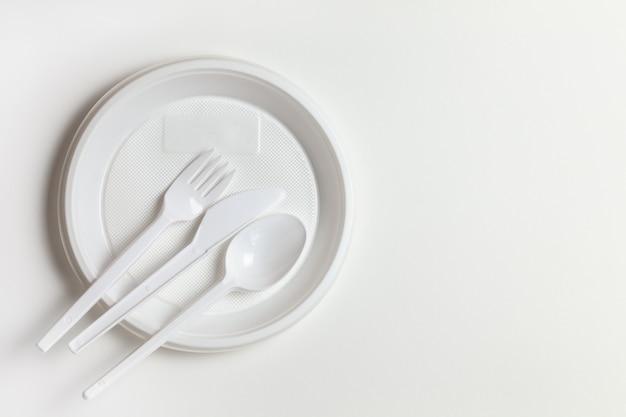 Piatti bianchi di plastica usa e getta, piatto, cucchiaio, coltello, forchetta su sfondo bianco