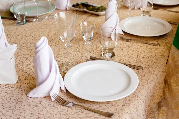 Piatti bianchi vuoti con tovaglioli, bicchieri da vino, forchette, coltelli, primo piano, posate sul tavolo del banchetto nel ristorante