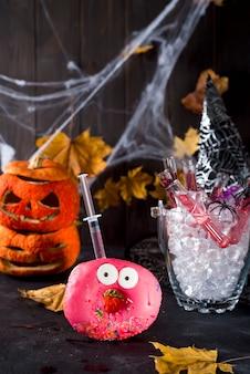 Piatti con ciambelle glassate, con un cocktail rosso in un tubo di vetro in un secchio di ghiaccio