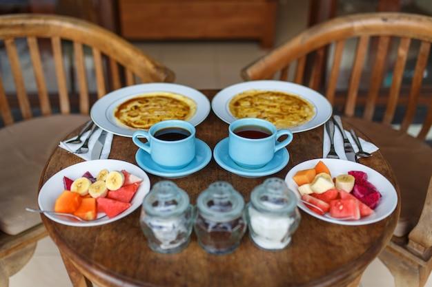 Piatti con pancake alla banana, frutti tropicali e due tazze di caffè sul tavolo di legno.