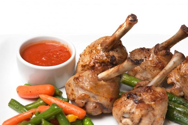 Piatti di carne arrosto con verdure e spezie isolati