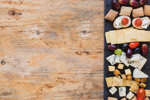 Piatti di formaggio su tavola di ardesia nera sopra il tavolo