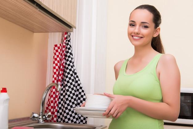 Piatti di lavaggio della giovane donna della moglie in cucina