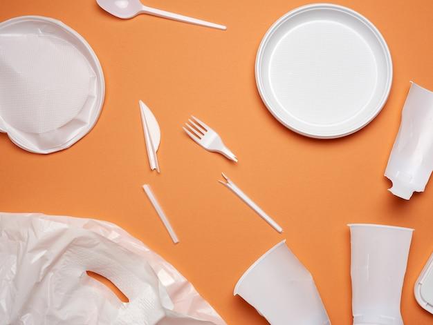 Piatti di plastica usati, pezzi di plastica e un sacchetto di plastica bianco su uno sfondo arancione