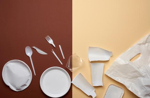 Piatti di plastica usati, pezzi di plastica e un sacchetto di plastica bianco su uno sfondo marrone, vista dall'alto