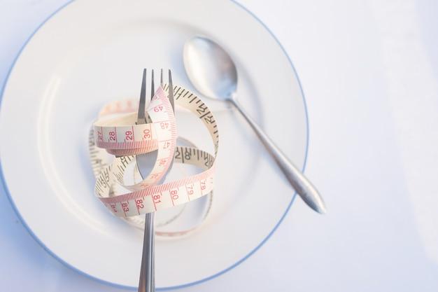Piatti di ricette dietetiche per mangiare. la forchetta è avvolta in un nastro di misurazione giallo sul piatto con un cucchiaio