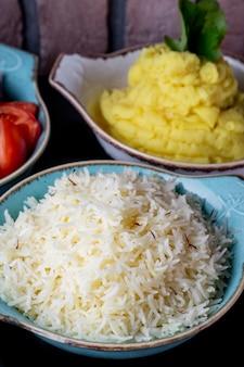 Piatti di riso e purè di patate serviti con insalata fresca