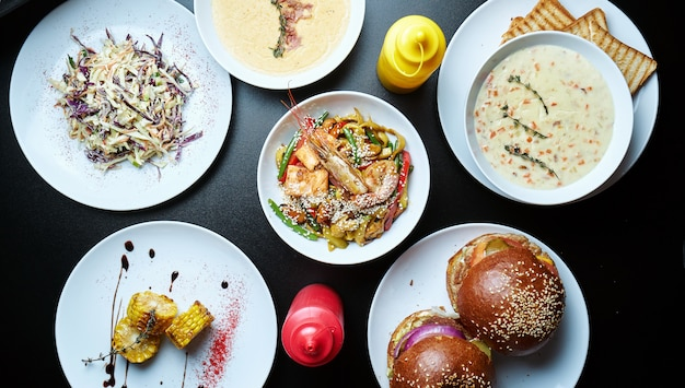 Piatti diversi assortiti su una superficie nera. tavolo da pranzo con hamburger, zuppe di crema, noodles al wok, insalata di insalata di cavolo e mais grigliato. vista dall'alto, cibo piatto disteso
