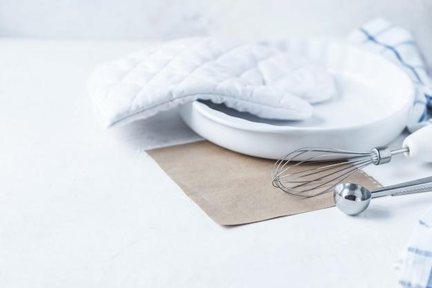Piatti e accessori da cucina per la cottura sul tavolo della cucina su uno sfondo bianco