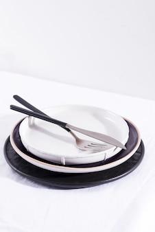Piatti e coltelleria ceramici fatti a mano sulla tavola bianca del tessuto, spazio della copia