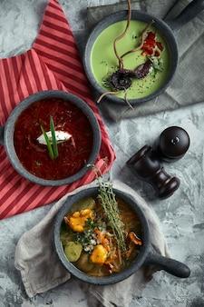 Piatti grigi con diverse zuppe su un grigio. piatto con zuppa di asparagi con polpo, un piatto di borscht tradizionale con panna acida, un piatto con zuppa di funghi e in piedi su multicolore