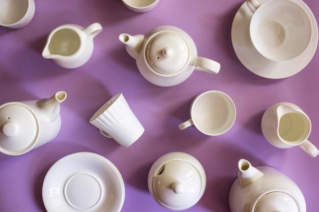 Piatti minimalista elegante bianco per caffè e tè su uno sfondo luminoso viola. concetto di articoli per la tavola. vista dall'alto