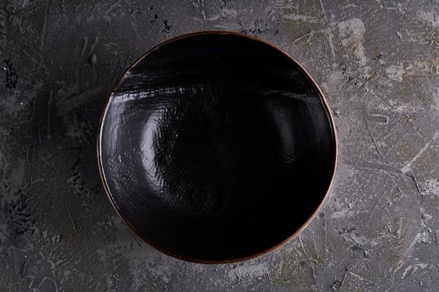 Piatti neri su sfondo grigio vertcal copia spazio