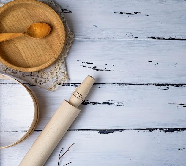 Piatti rotondi in legno, setaccio e mattarello