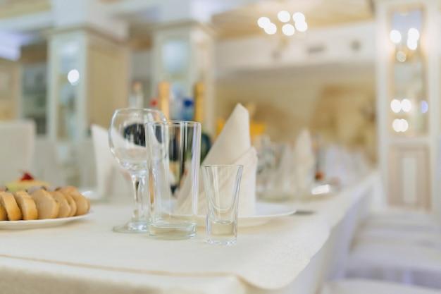 Piatti su tavoli per banchetti, che servono bicchieri, cucchiai e piatti