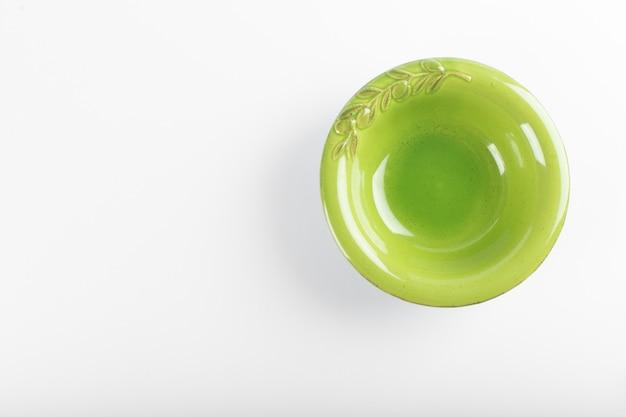 Piattino verde vuoto su un bianco