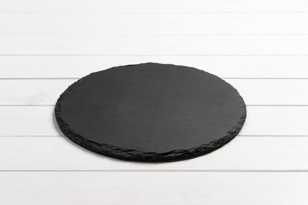 Piatto ardesia sul tavolo. pietra ardesia nera su fondo di legno. copia spazio