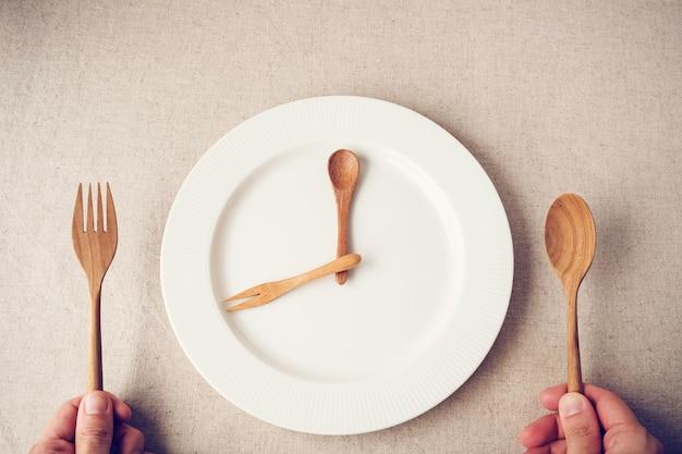 Piatto bianco con cucchiaio e forchetta, concetto di digiuno intermittente