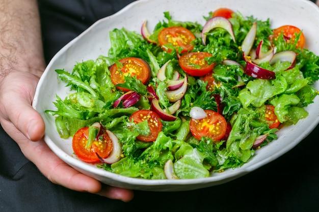 Piatto bianco con insalata di lattuga, pomodorini e cipolla rossa con olio d'oliva, salsa di senape e aceto di vino