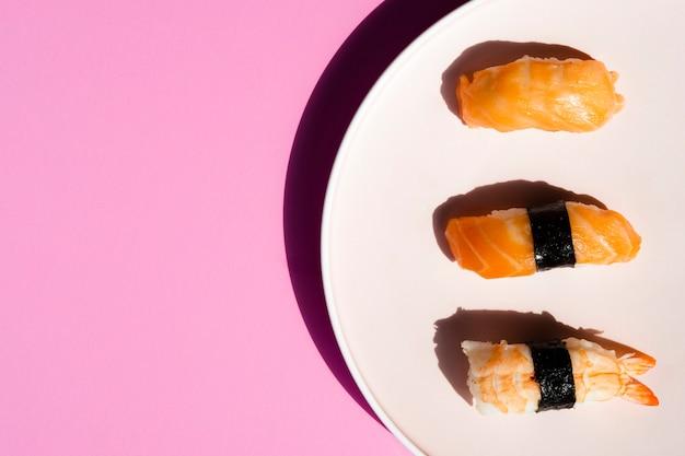 Piatto bianco con sushi su sfondo rosa